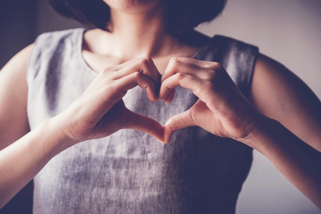 A woman making a heart with her hands in front of herself.