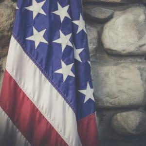 An American flag against a cobblestone wall