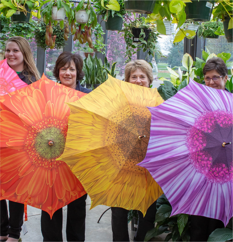 Wedel's team holding colorful umbrellas in front of a large floral design
