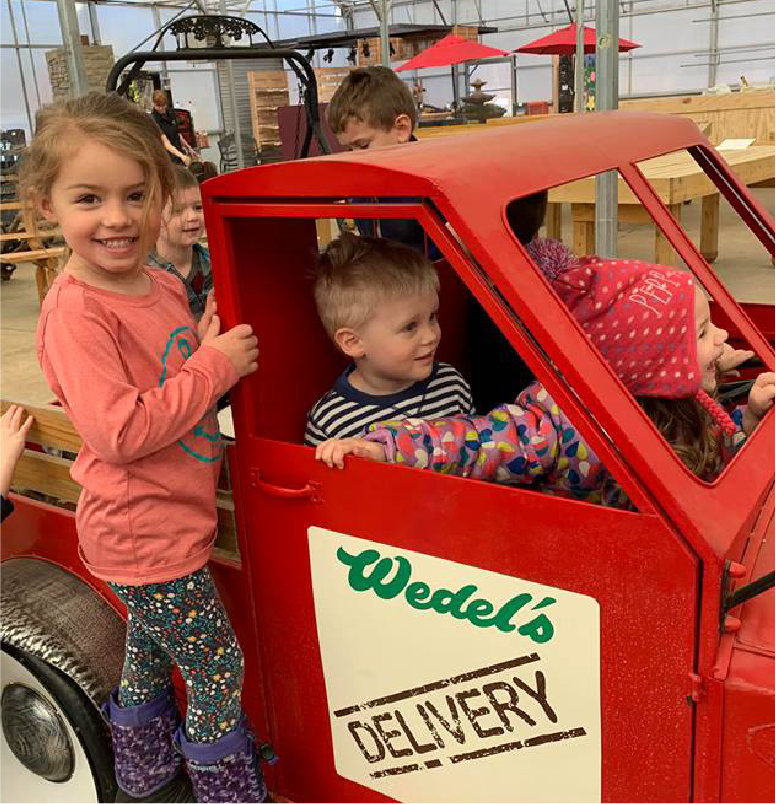3 kids in a red Wedel's small truck