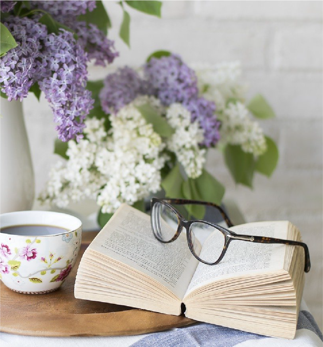 Full cup of coffee with floral design next to an open book with glasses and purple floral piece hanging elegantly over the top left