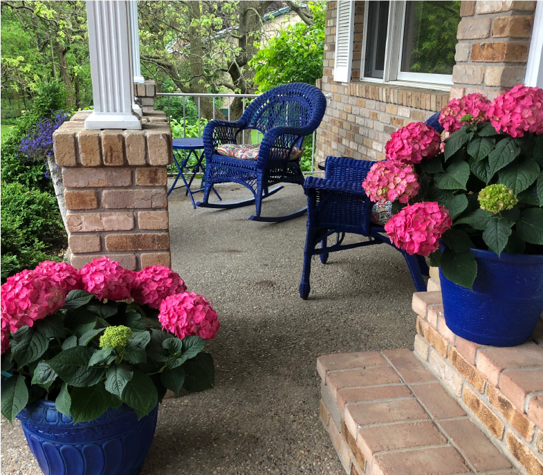 Stone home porch with potted flowers making the area look beautiful
