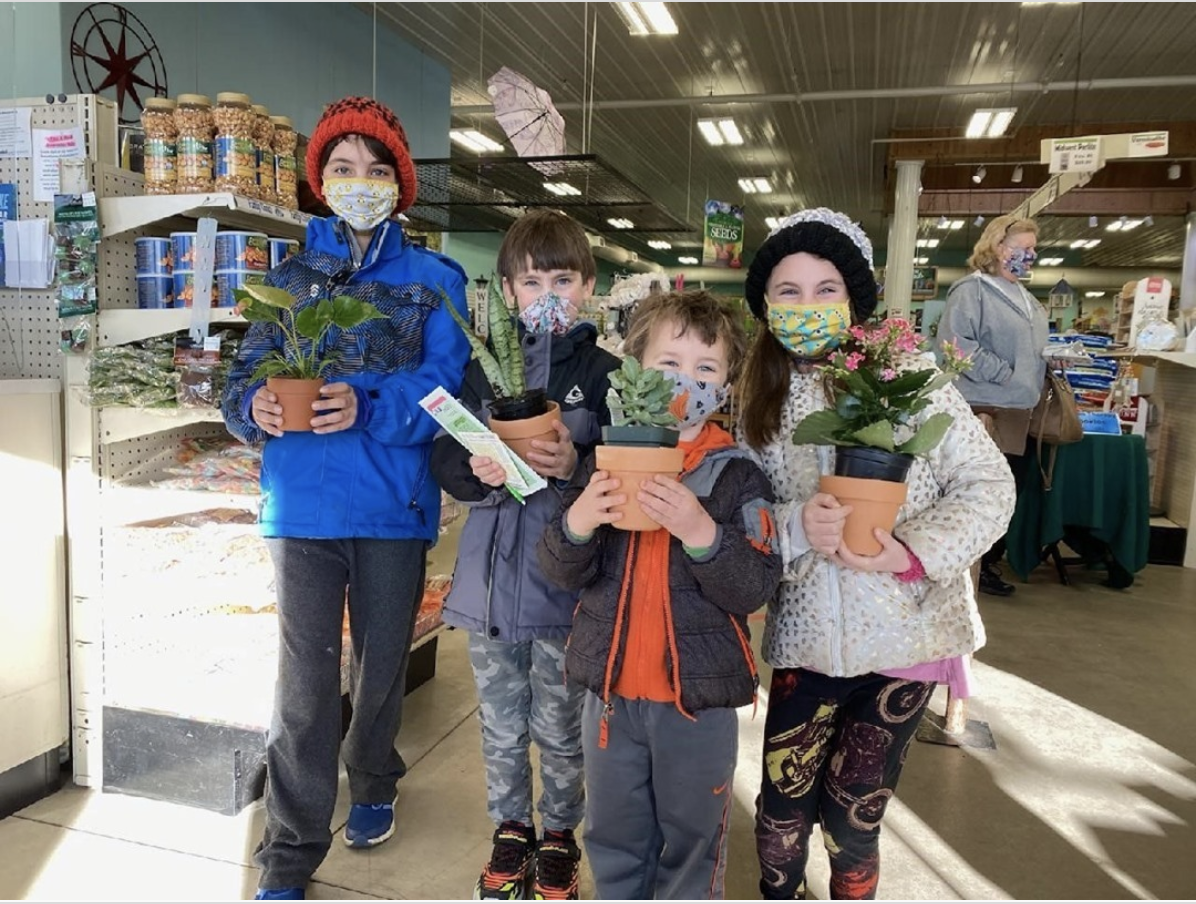 4 kids with holding Wedel's potted plants