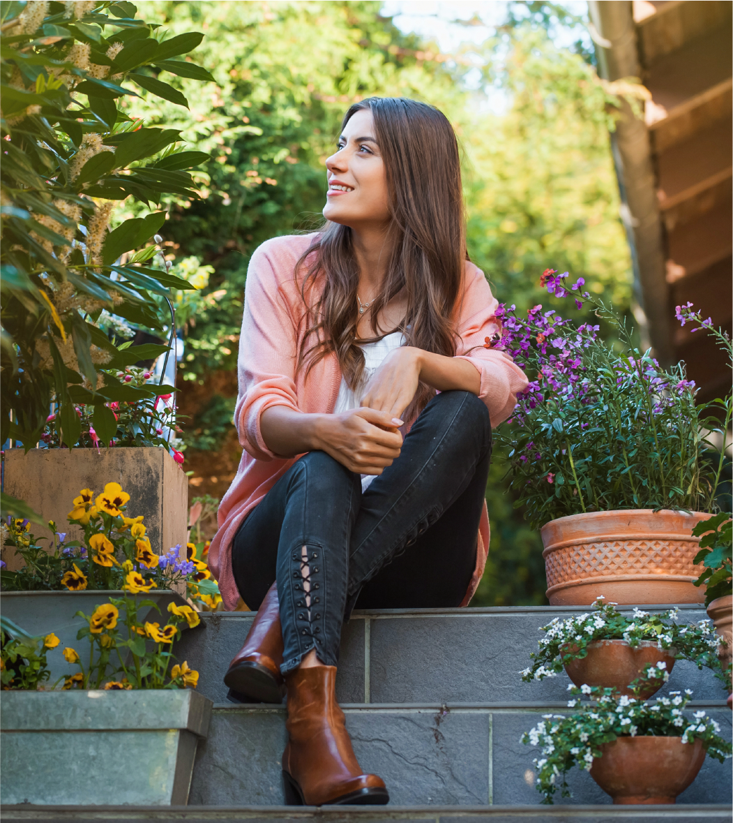 Woman wearing pink shirt, brown boots, and dark leggings looking to her right surrounded by beautiful purple, yellow, and white potted plants
