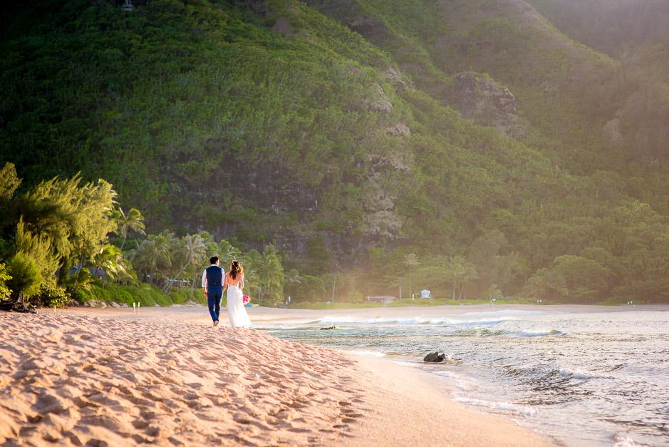Couple photographed walking on a Kauai beach.