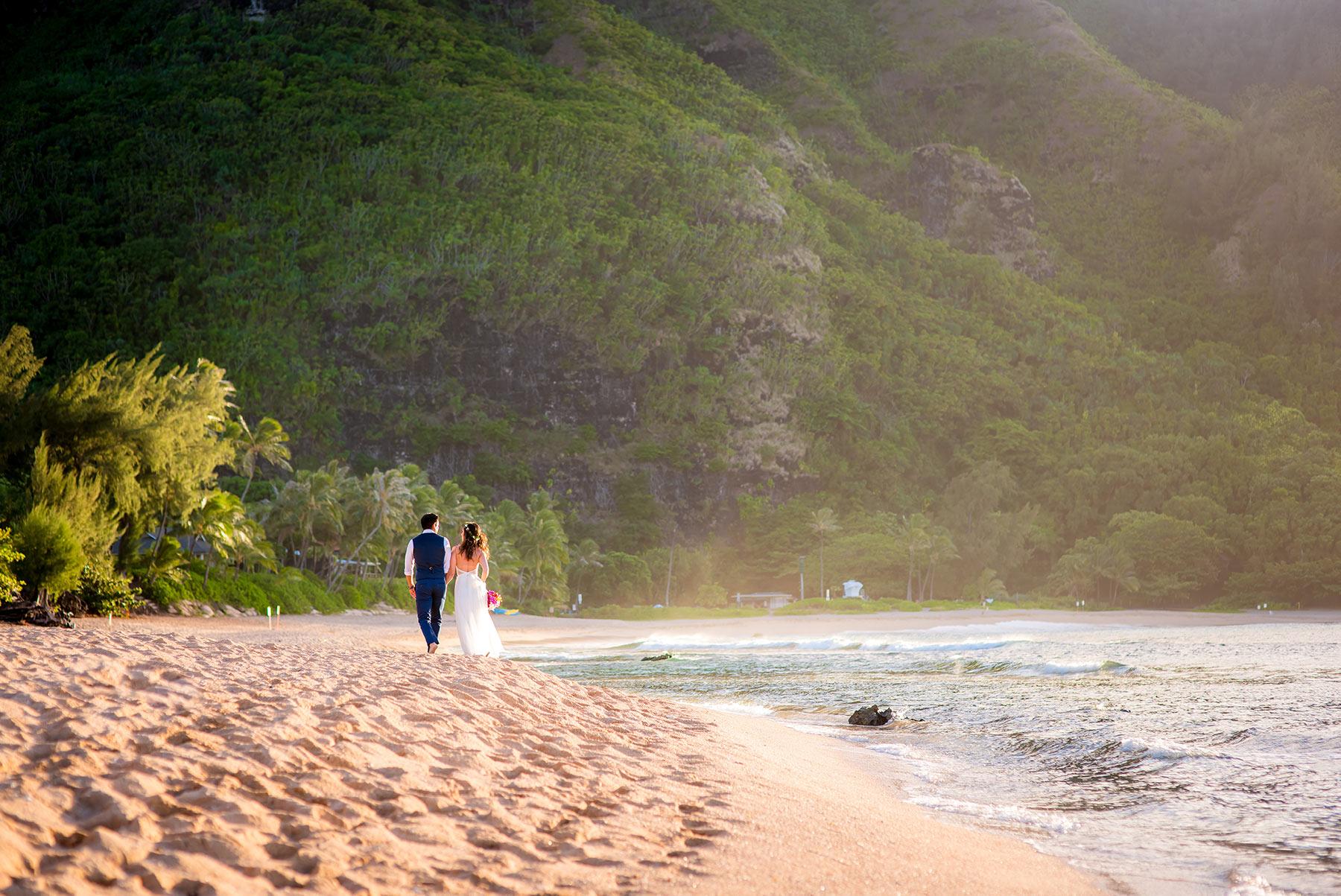 A couple walking off into the sunset at Kee beach, Kauai - on their perfect Hawaiian wedding day.