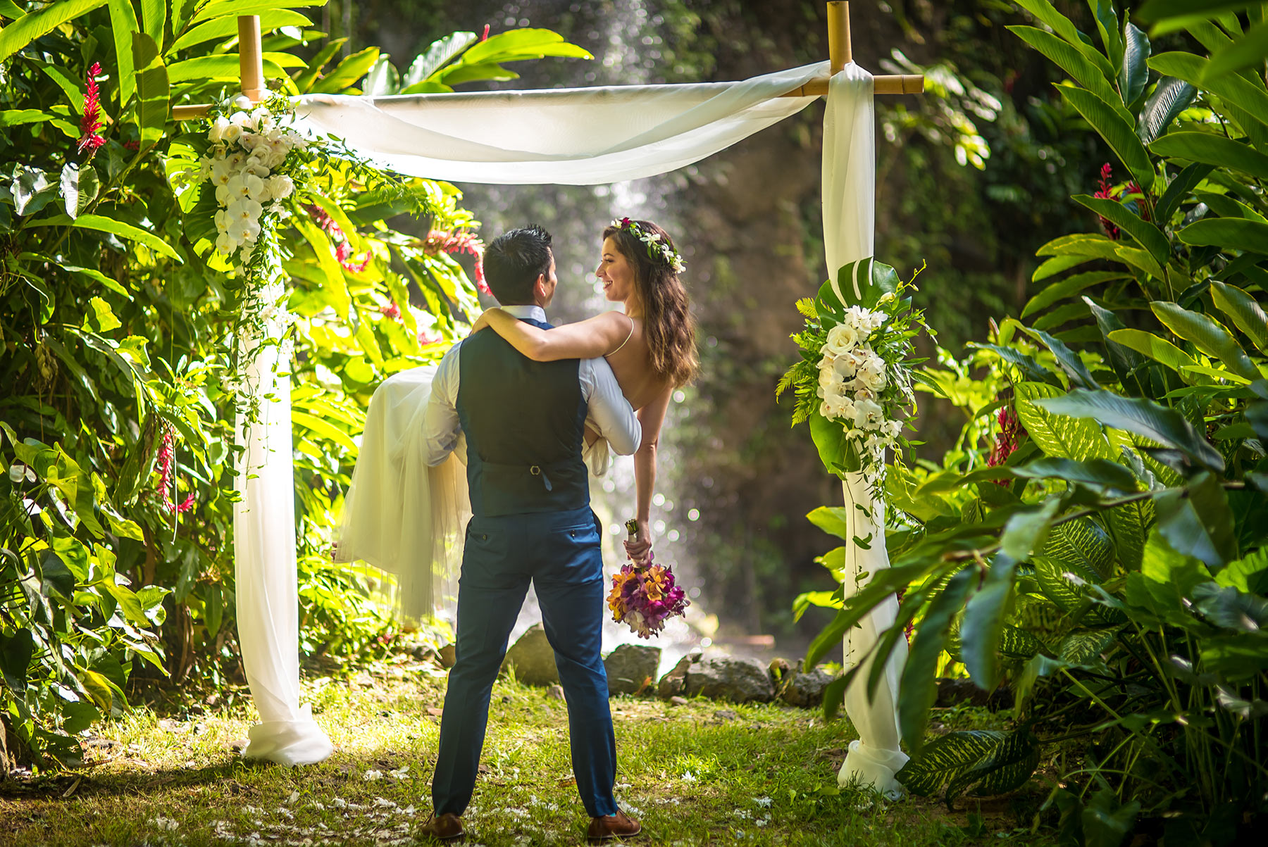 The groom majestically holds his bride in the Hawaiian flower lei arch - this is the wedding of her dreams.