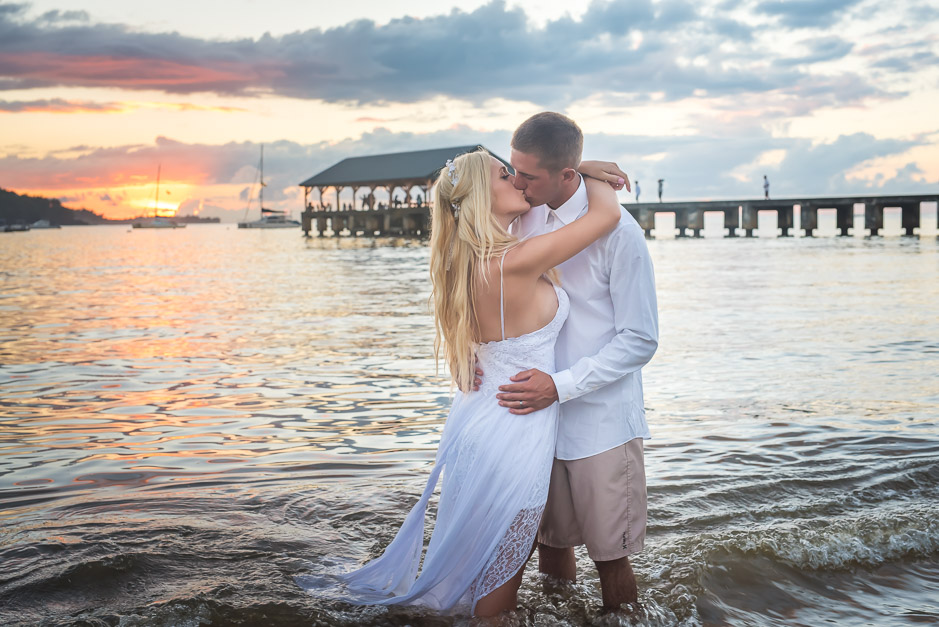 The husband and wife share an intimate kiss as they play in the water for 'Trash-the-dress' photos