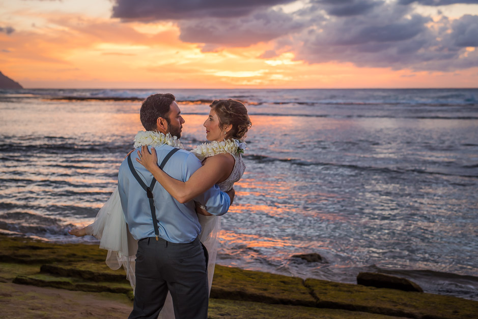 Couple photographed on beach during sunset in Kauai.