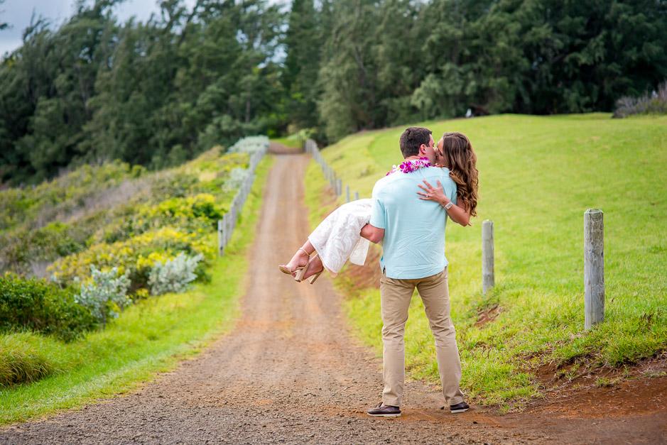 Husband carries his bride down a dirt path.