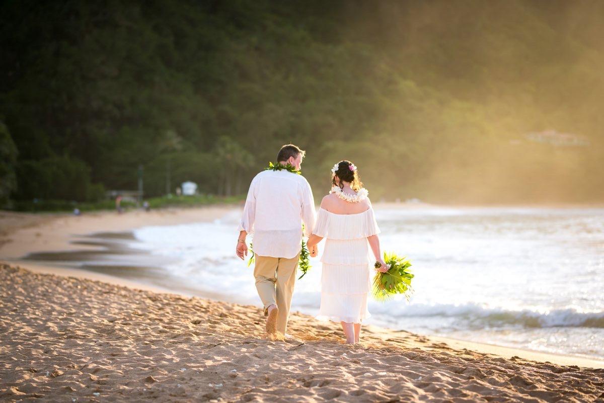 Couple walking on a beach in Kauai.