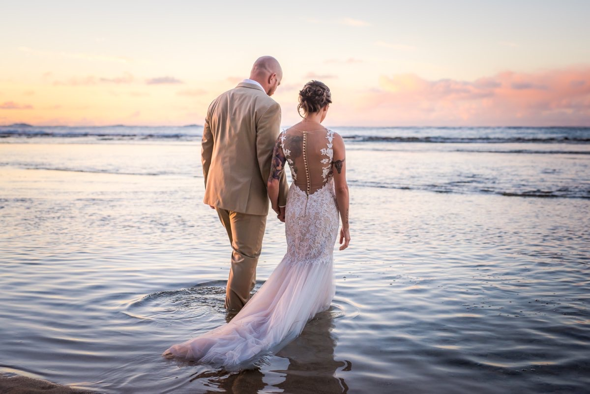 Wedding photo on a beach during sunset.
