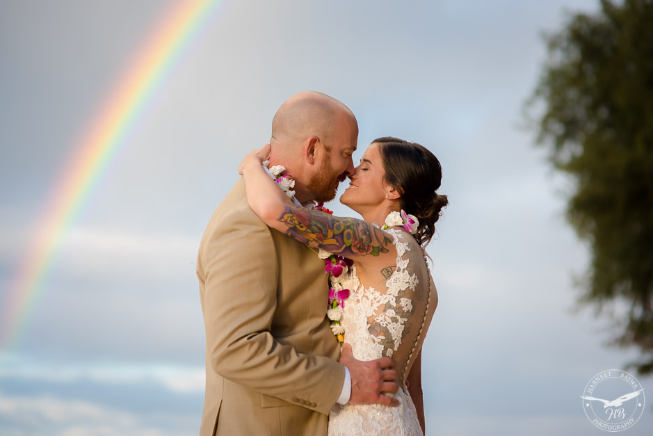 The lucky bride and groom pose in front of a rainbow that appeared just after they got married.