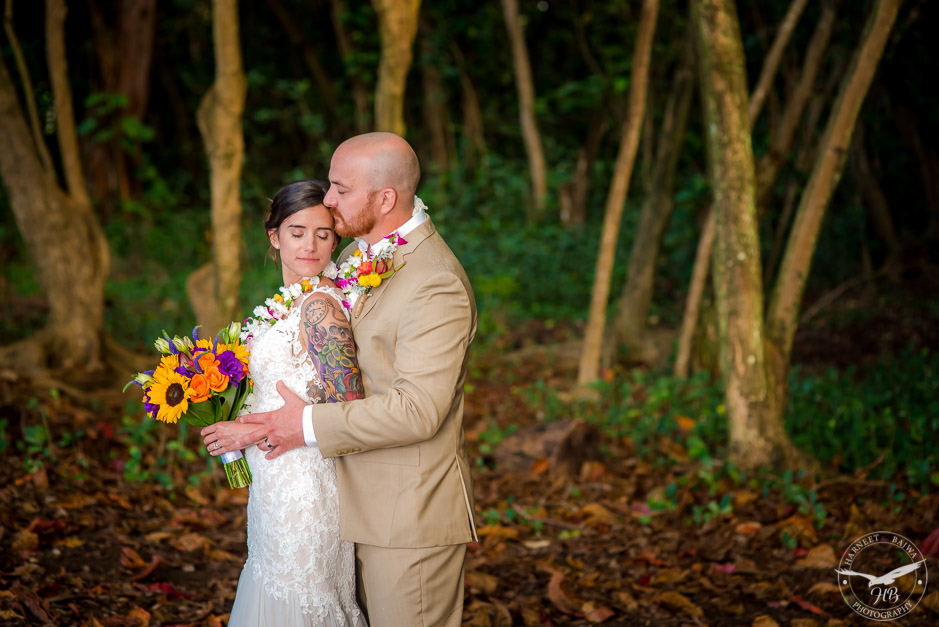 The bride and groom pose beautifully in front of the lush greens that are typical to the tropical Kauai.