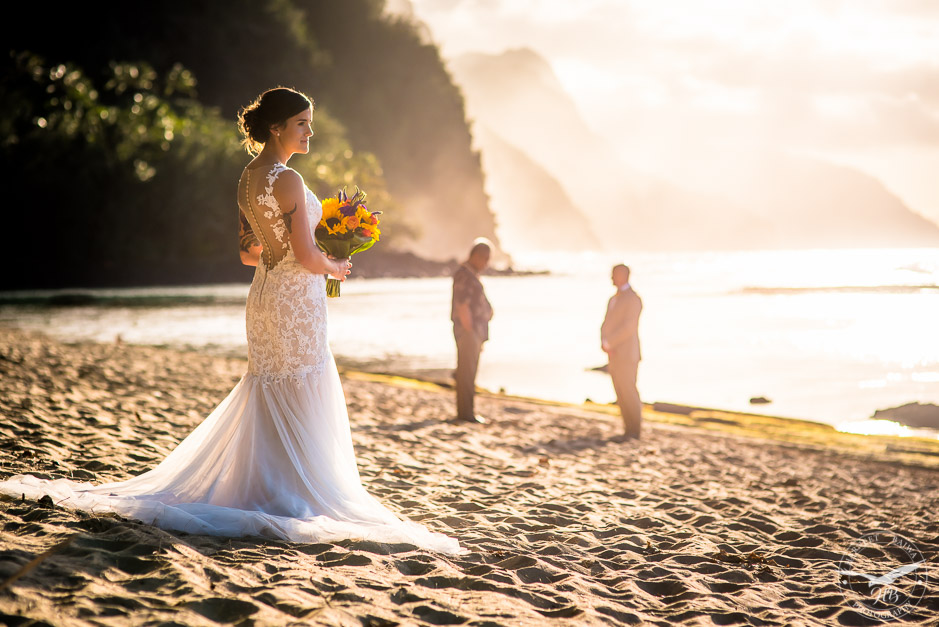 The beautiful bride about to walk down the beach to the waiting groom and officiant.