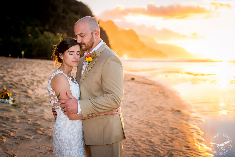 The bride and groom share an intimate embrace as the sky in the background is lit different shades of orange by the setting sun.