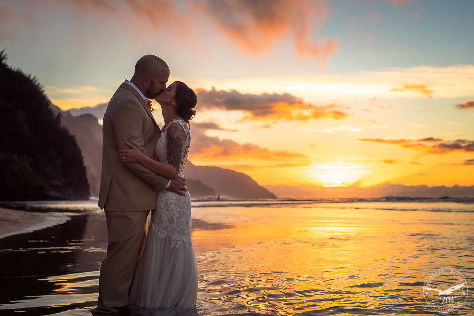 The bride and groom star a kiss as the sun sets over the water in the distance behind them.