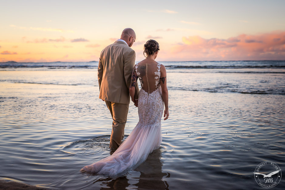 The newly married couple walking into the calm ocean as part of the 'trash the dress' shoot.