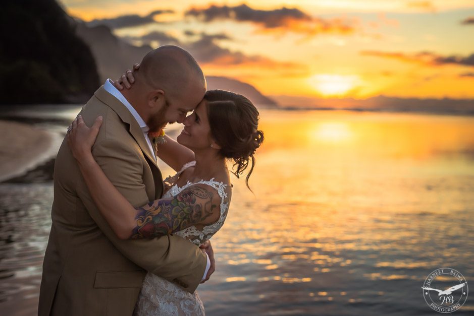 With the gorgeous sunset in the backdrop, the new married couple embrace and look into each others eyes.