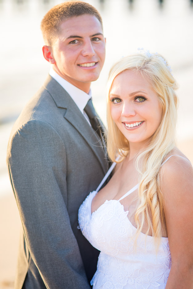 The newlyweds striking classic portrait pose as they look directly at the camera