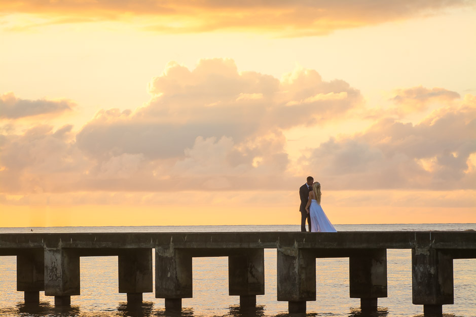 The newlywed young couple kiss s they stand on the famous Hanalei pier of Kauai.
