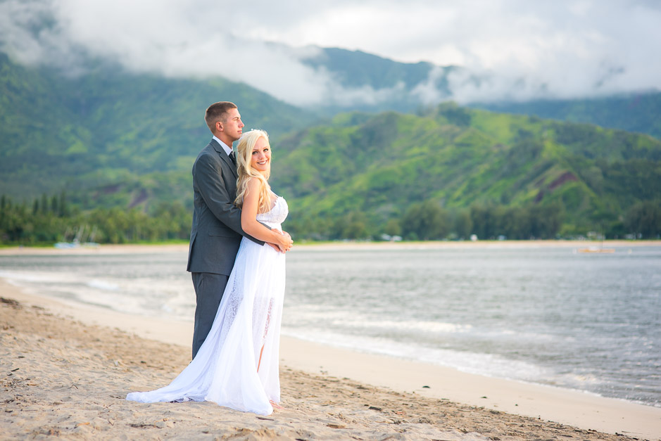 A young newlywed couple posing for the camera by the beach with the mountains in the backdrop.