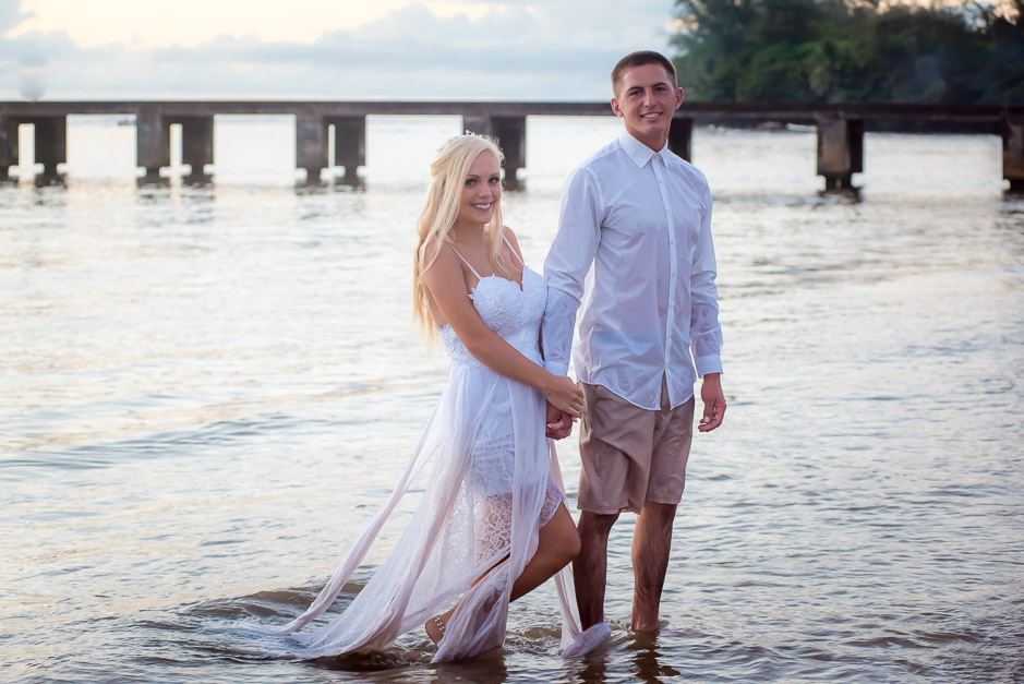 The newlywed couple coming out of the ocean after taking a dip in the water.