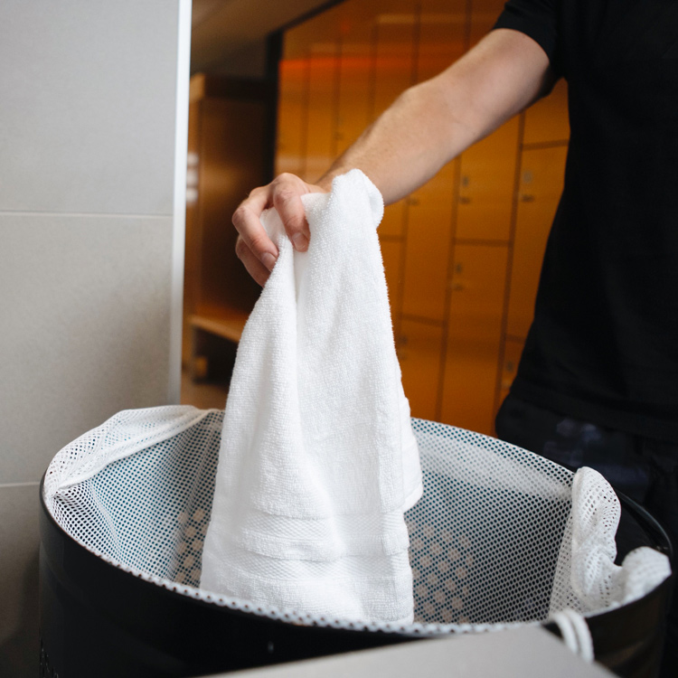 Person putting a used towel in the bin