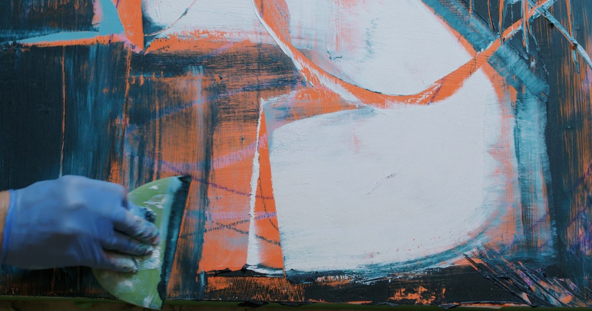 Blurry hand creating abstract art in dark blues, oranges, and whites.