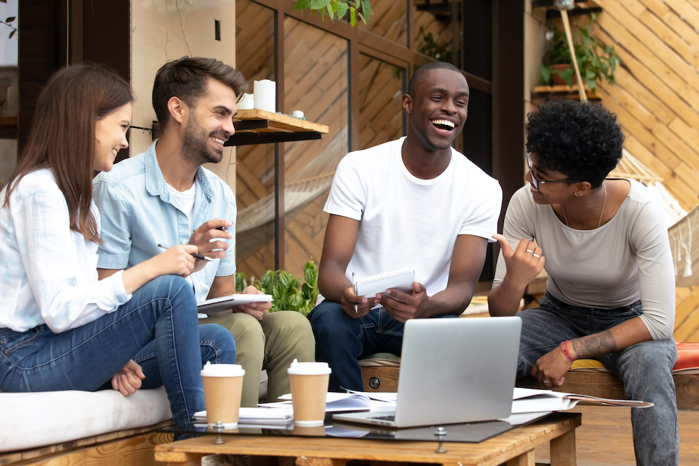A group of friendly coworkers laughing in front of a computer outside
