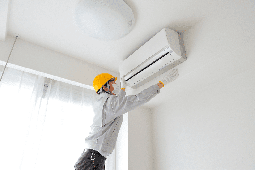man installing ductless air conditioner white room yellow hard hat hvac