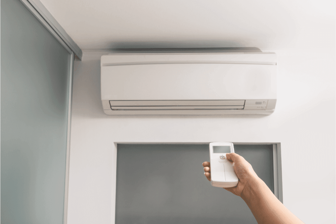 ductless ac remote control demonstration arm pointing toward air conditioner