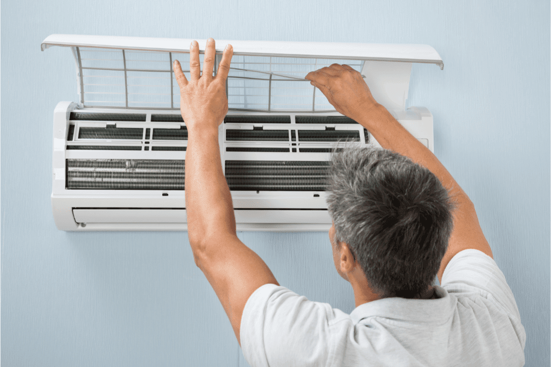man gray hair changing filter in ductless ac unit blue walls white shirt