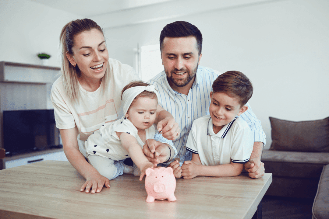 family smiling young children piggy bank saving money smiling laughing kitchen couch wooden table