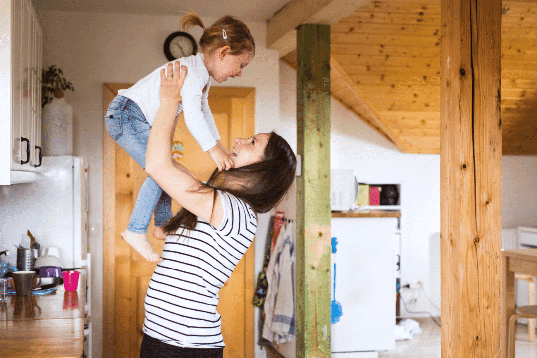 mother and daughter lifting in the air wooden interior kitchen striped shirt fun smiling happy