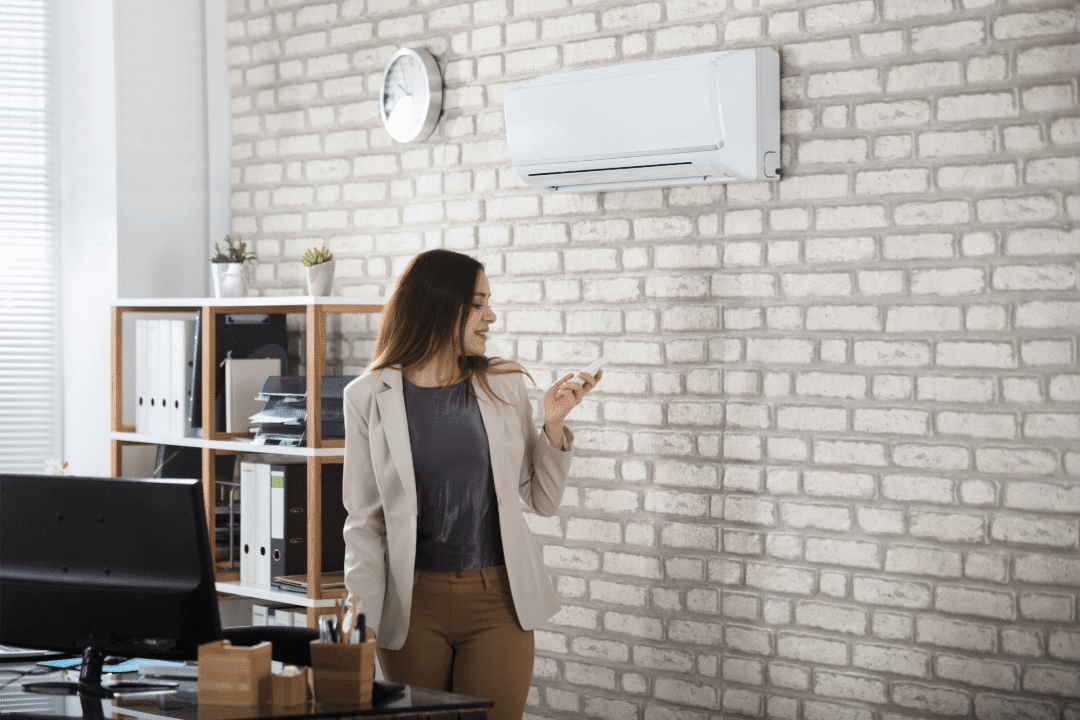 woman in office working controlling ductless ac unit with a remote control brick building modern