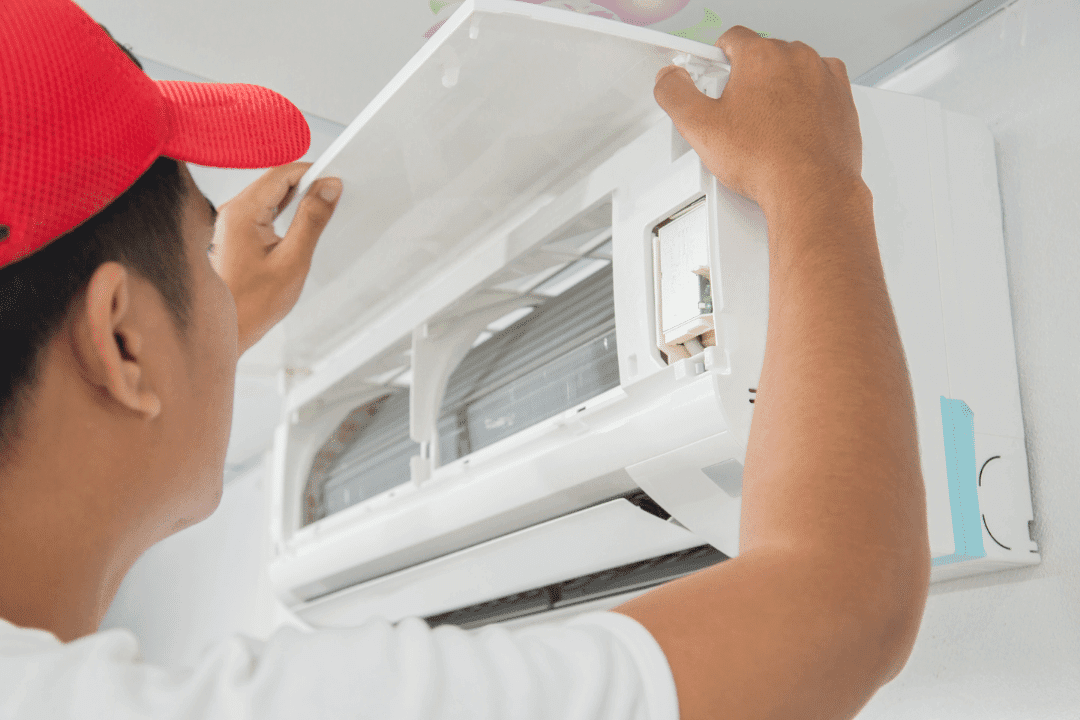 man with red hat closing lid on ductless air conditioning unit installation repair service
