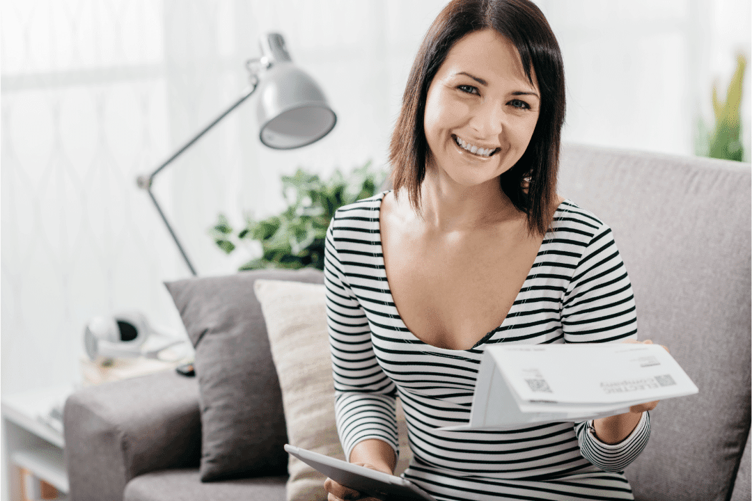 woman smiling saving money on energy bills in bright room striped shirt gray couch