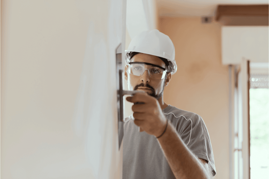 man doing home improvements applying plaster with a trowel
