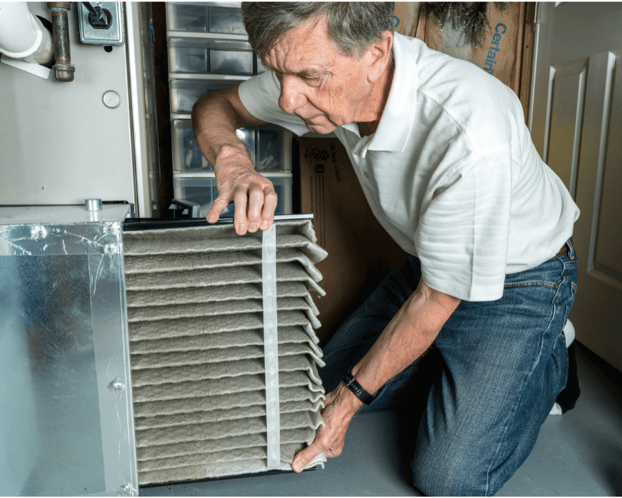 older man changing filer on old air conditioner ducted