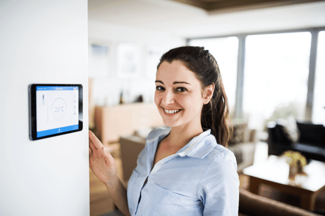 woman with smart home thermostat smiling in living room