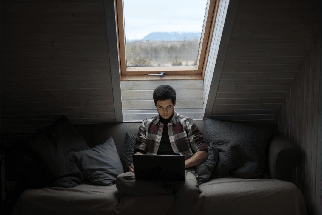 man in attic bedroom with laptop skylight