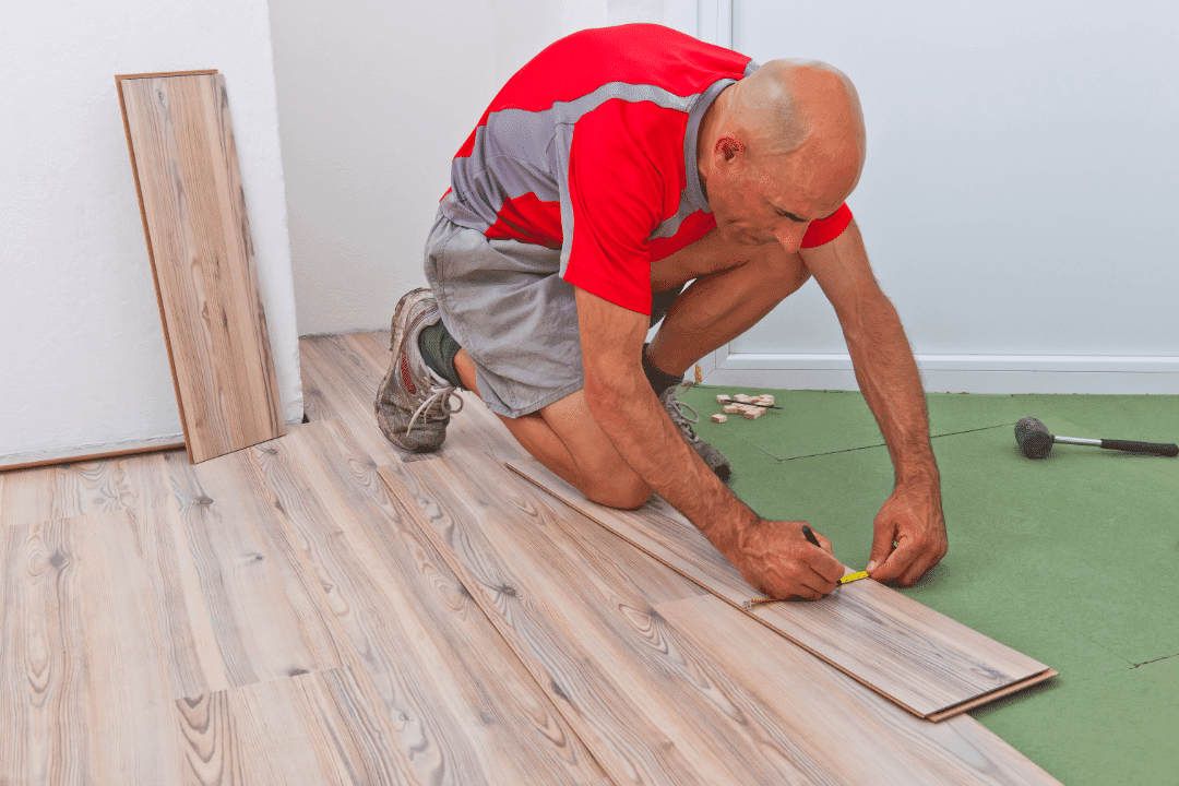 man measuring flooring in home addition