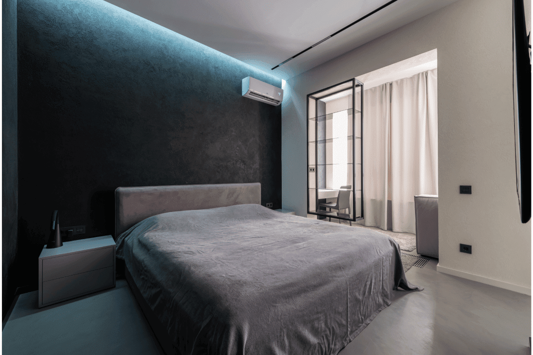 bed with gray covers ductless ac with backlight