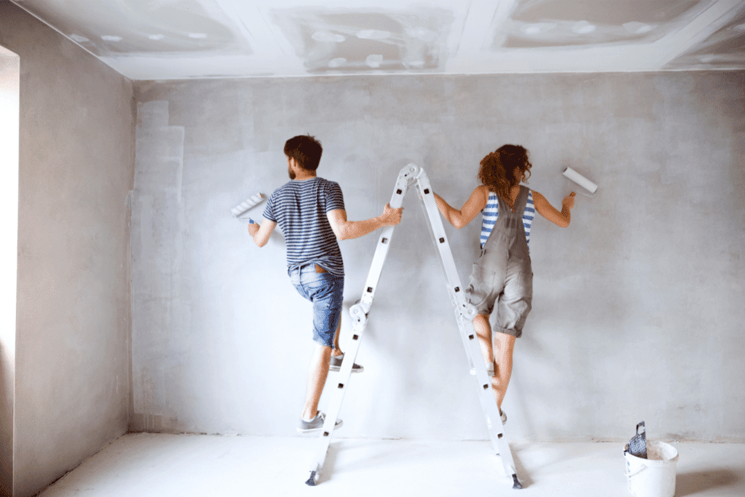 young couple painting walls home renovation