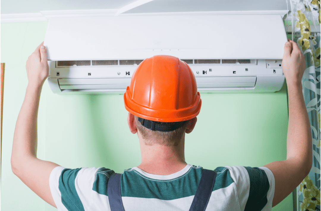 technician hard hat putting hood on ductless AC