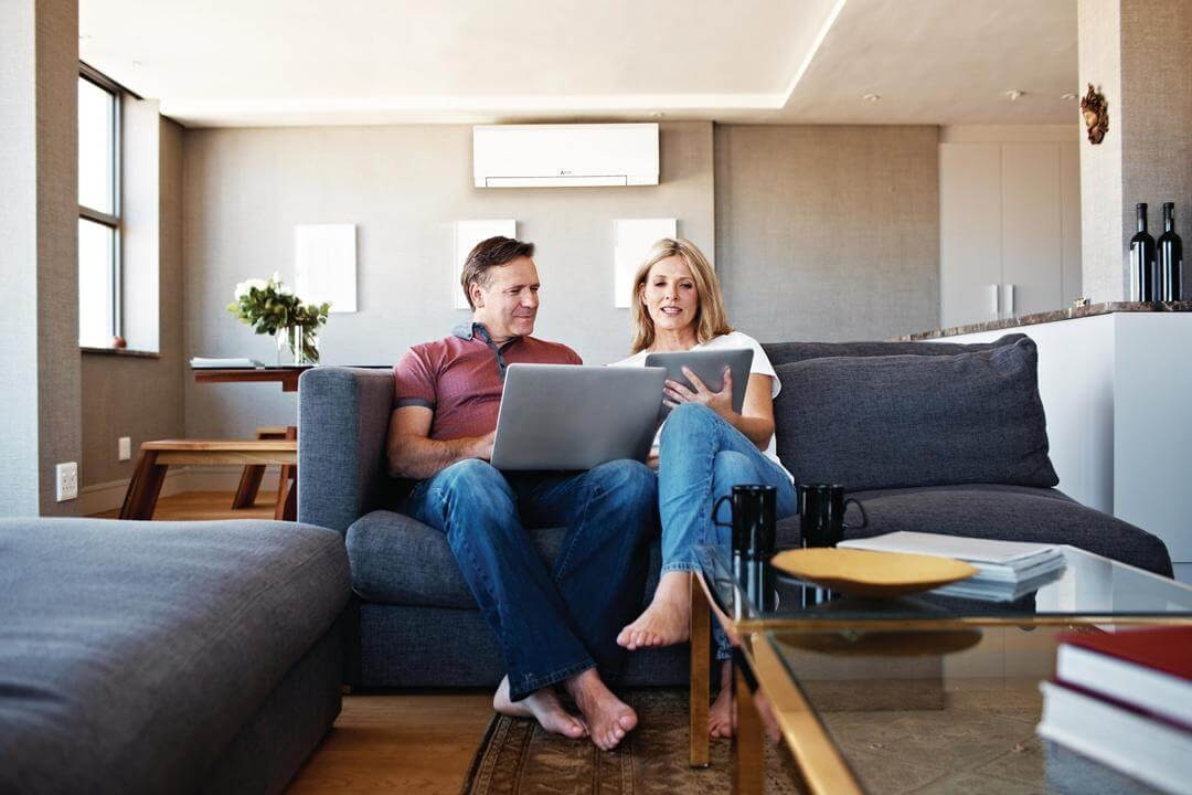 couple sitting on couch with tablet and laptop ductless ac in background