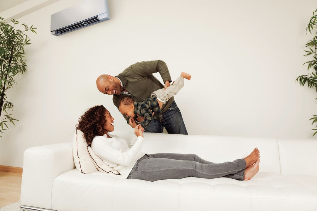 family father holding child above couch mother lying on couch ductless AC