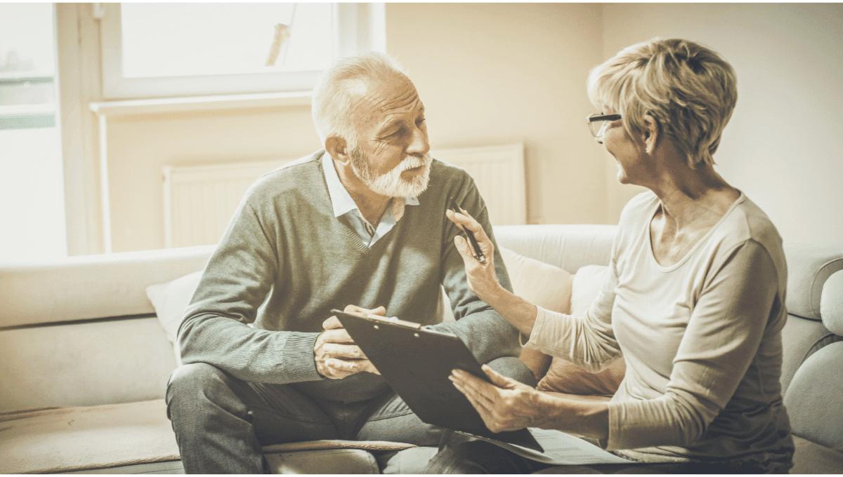 older couple talking about finances clipboard negotiation