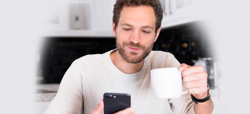 Mann trinkt Kaffe und schaut dabei auf sein Telefon